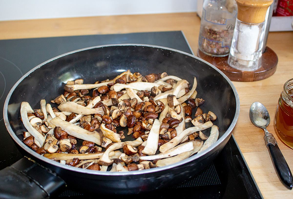 mushrooms being fried in a pan with ghee