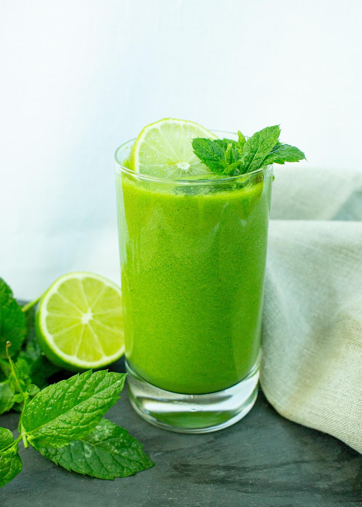 Smoothie mit grüner Melone, Minze und Limette in einem Glas mit Limettenscheibe und Minzblättern, im Hintergrund ein graues Leinentuch
