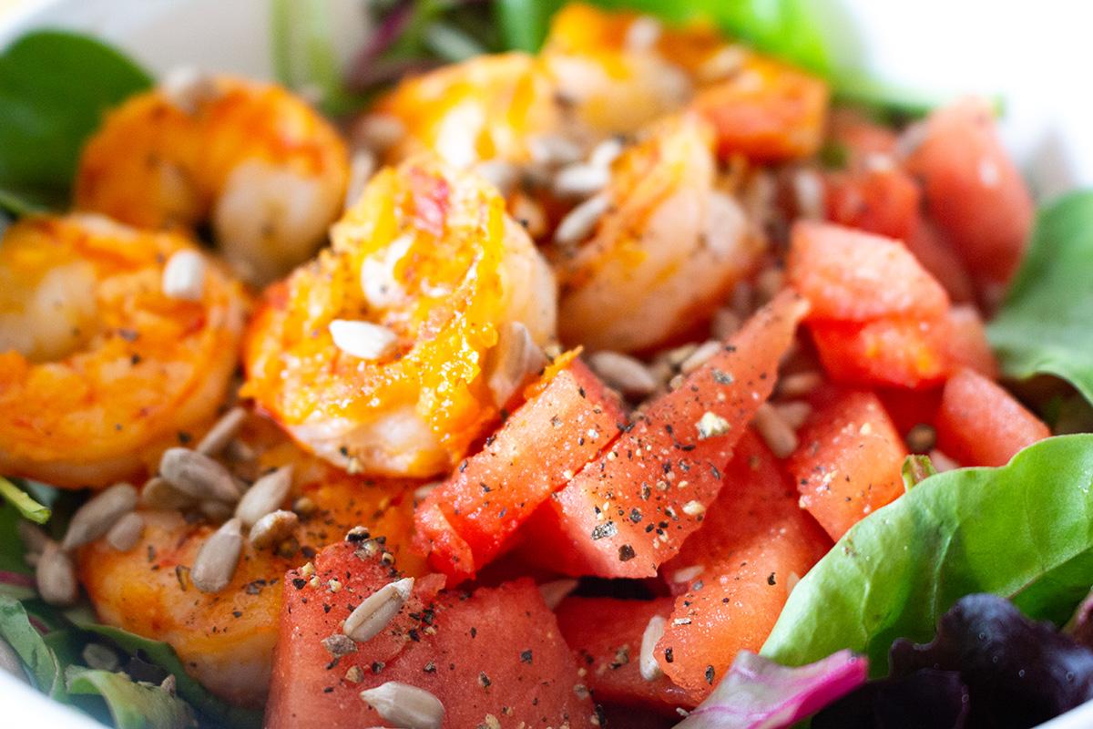 gebratene Garnelen in Knoblauch, Wassermelone mit Pfeffer gewürzt auf grünem Salat