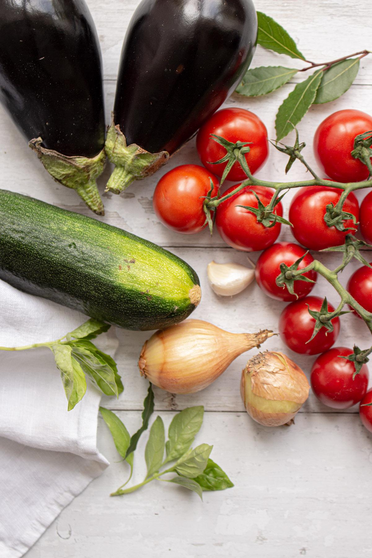 Aubergine, Zucchini, Tomaten, Knoblauch und Zwiebeln auf weißem Holzuntergrund